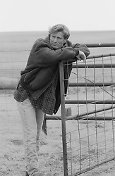 Man outdoors on a ranch leaning against a fence