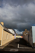 """Rainclouds over coloured houses on street, Kilkee, Co. Clare, Ireland This mage can be licensed via Millennium Images. Contact me for more details, or email mail@milim.com For prints, contact me, or click """"add to cart"""" to some standard print options."""