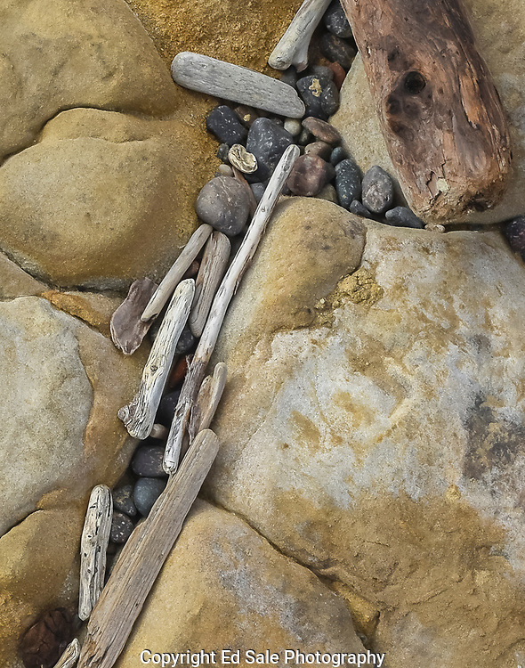 The interplay of stones, sandstone, driftwood and a log form interesting lines and shapes on Weston Beach at Point Lobos, California