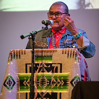 """Shiprock Chapter President and author of """"A Line Drawn in The Rez Dirt"""" Duane 'Chili' Yazzie, at the podium, welcomes the audience in attendance. The """"Education is our Human Right"""" forum was held at the Phil L. Thomas Performing Arts Center in Shiprock on Thursday."""