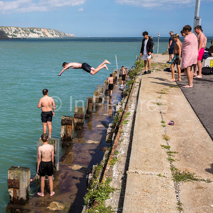 A boy dives off Folkestone Harbour into the sea water with his friends watching after the annual Trawler race and fun day in Folkestone, Kent, England, United Kingdom. The White Cliffs of Dover can be seen in the background.