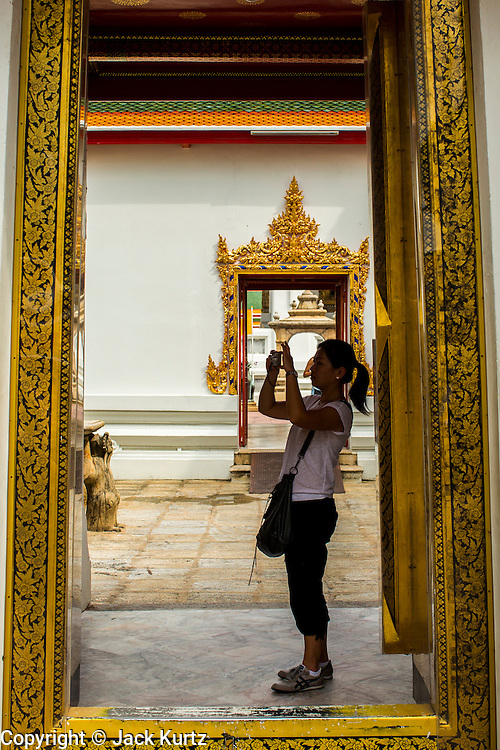 26 NOVEMBER 2012 - BANGKOK, THAILAND: A tourist takes pictures in a doorway at Wat Pho in Bangkok. Thailand's Temple of the Reclining Buddha has gained further global prominence following a 45-minute tour by U.S. President Barack Obama and Secretary of State Hillary Clinton during their November 18-19 visit to the kingdom. Known also as the Temple of the Reclining Buddha, its official name is Wat Phra Chettuphon Wimon Mangkhlaram Ratchaworamahawihan. The temple is also known as the birthplace of traditional Thai massage. There is a popular massage school on the temple grounds.     PHOTO BY JACK KURTZ
