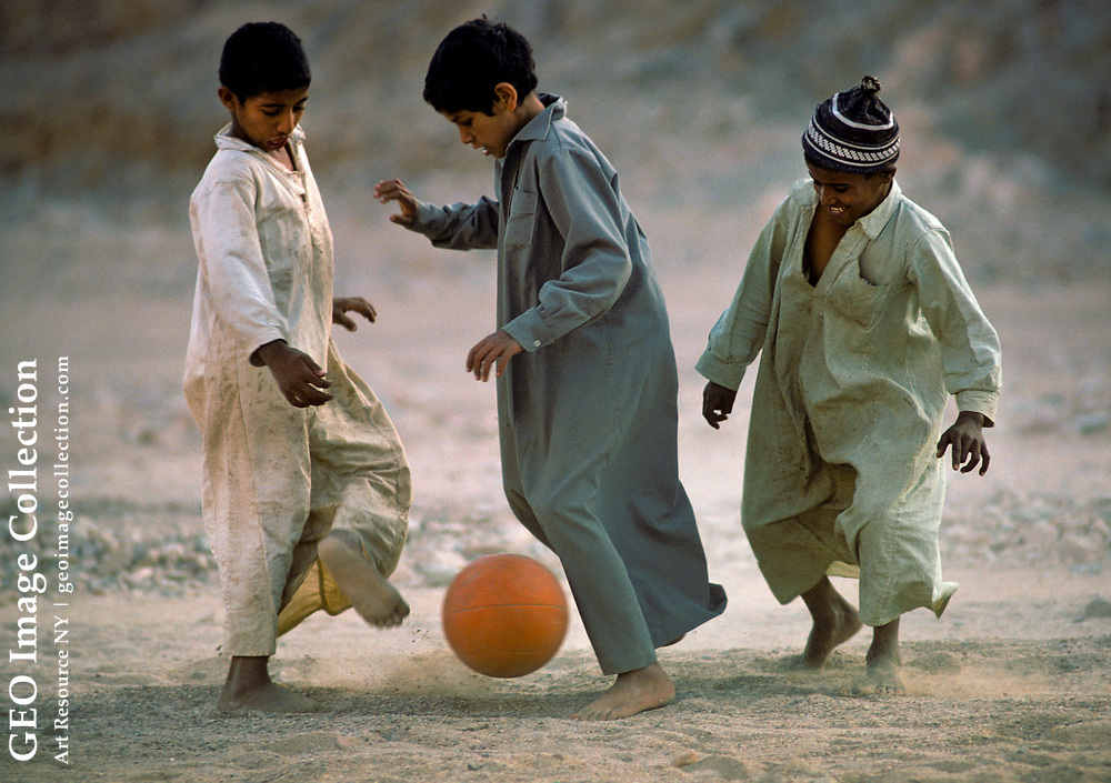 Bedouin Arab nomad boys playing soccer at an encampment in the Wadi Feiran oasis in the Sinai Peninsula, Egypt. The young children are wearing traditional long Bedouin garments and kicking a ball. The barefoot boys are happy and laughing and appear to enjoy the sport.