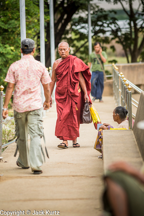 23 MAY 2013 - MAE SOT, TAK, THAILAND:  A Burmese Buddhist monk walks along the Moie River promenade towards towards a boat landing so he could return to Myawaddy, Myanmar. Fifty years of political turmoil in Burma (Myanmar) has led millions of Burmese to leave their country. Many have settled in neighboring Thailand. Mae Sot, on the Mae Nam Moie (Moie River) is the center of the Burmese emigre community in central western Thailand. There are hundreds of thousands of Burmese refugees and migrants in the area. Many live a shadowy existence without papers and without recourse if they cross Thai authorities. The Burmese have their own schools and hospitals (with funding provided by NGOs). Burmese restaurants and tea houses are common in the area.      PHOTO BY JACK KURTZ