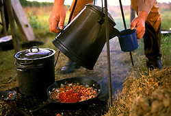 Stock photo of a man pouring a hot cup of coffee from a pot over a hot coals
