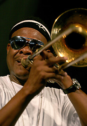 30 April 2006. New Orleans, Louisiana. Jazzfest . <br /> The first New Orleans Jazz and Heritage festival following the disaster of Hurricane Katrina. <br /> Legendary local jazz trombonist Corey Henry plays with Kermit Ruffins and the Barbecue Swingers plays at the Bellsouth WWOZ Jazz tent.<br /> Photo ©Charlie Varley/varleypix.com<br /> All rights reserved.