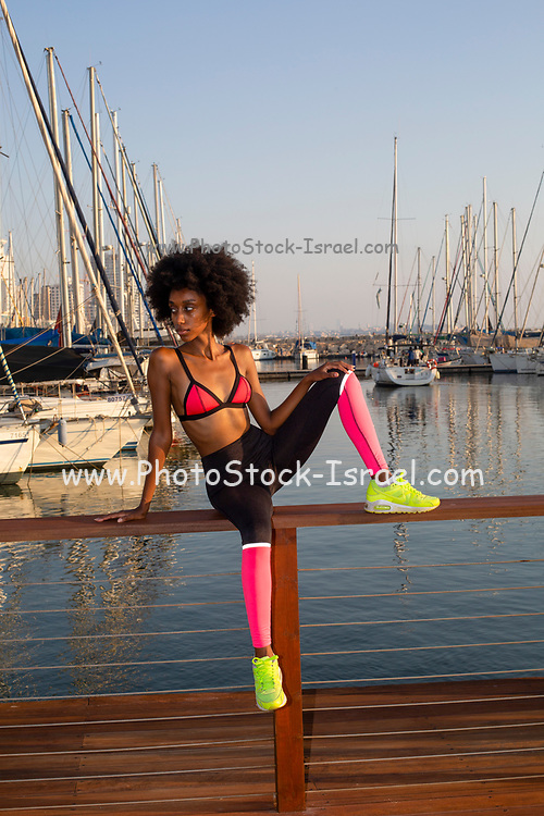 Young african woman resting after an outdoor workout. The yachts in the Tel Aviv Marina the background