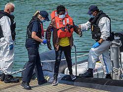 © Licensed to London News Pictures. 21/07/2021. Dover, UK. A migrant is helped by Border Force officers as he is brought ashore at Dover Harbour in Kent after crossing the English Channel. It is being reported that at least 430 migrants crossed the English Channel to the UK on Monday, a new single day record. Photo credit: Stuart Brock/LNP