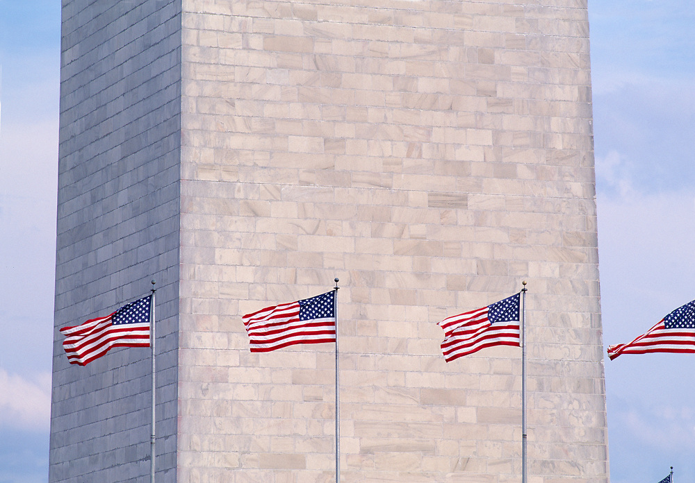 Lower section of the Washington Monument with a row of American Flags blowing in the wind