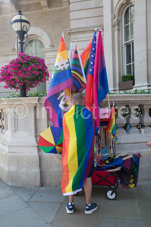 A man selling rainbow flags during the Pride in London parade outside The Langham hotel on the 7th July 2018 in central London in the United Kingdom. 30,000 marched through central London for the city's annual LGBT Pride celebration.