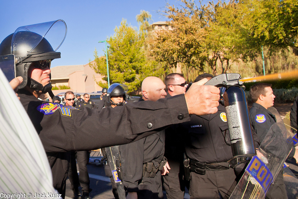 30 NOVEMBER 2011 - PHOENIX, AZ:    Phoenix police pepper spray the crowd at an anti-ALEC protest Wednesday. Police pepper sprayed the crowd several times and arrested six or seven people during the melee. About 300 people picketed the American Legislative Exchange Council (ALEC) conference at the Westin Kierland Resort and Spa in Phoenix, AZ, Wednesday. The protesters claim ALEC, a conservative think tank, violates its tax exempt status by engaging in lobbying, a charge ALEC officials deny. Many conservative pieces of legislation, like Arizona's anti-immigration bill SB1070, originate with ALEC conferences (SB 1070 originated at an ALEC conference several years ago). Many of the protesters are also members of the Occupy movement.  PHOTO BY JACK KURTZ