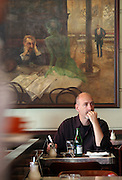 "Gast im berühmten Kaffeehaus SLAVIA in der Prager Innenstadt. Im Hintergrund das Gemälde ""Der Absinthtrinker"" von Maler Viktor Oliva.<br /> <br /> Visitor at the famous Café Slavia in the city centre of Prague. In the back a painting by Viktor Oliva with the title the Absinth drinker."