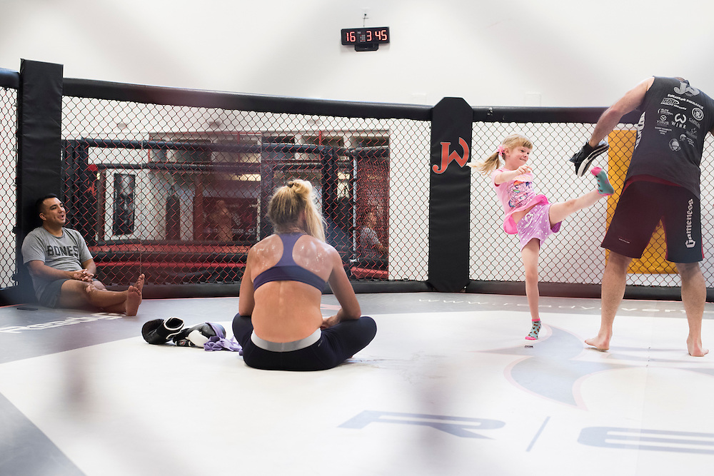 Coach Mike Winkeljohn plays with his daughter while Wrestling coach Izzy Martinez and UFC bantamweight Holly Holm look on after a training session at Jackson Wink MMA in Albuquerque, New Mexico on June 10, 2016.