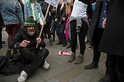 Street man enjoying the party atmosphere sitting cross legged amongst the crowd at the Peoples Assembly Against Austerity demonstration against cuts for health, homes, jobs and education onSaturday April 16th in London, United Kingdom. Tens of thousands of people gathered to protest in a march through the capital protesting against the Conservative Party cuts. Almost 150Councillors fromacross the countryhave signed a letter criticising the Government for funding cuts and and will be joining those marching in London. The letter followed the recent budget in which the Government laid out plans to cut support for disabled people while offering tax breaks for big business and the wealthy.