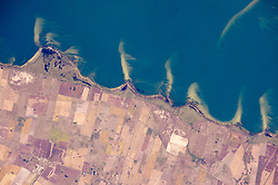 """While in orbit over the Brazilian coast, an astronaut aboard the International Space Station took this photograph of some of the country's famous coastal lagoons. This view shows a short 20-kilometer (12-mile) stretch of a lagoon shoreline where pointed sand spits jut into waters of Mangueira Lagoon (Lagoa Mangueira). The ends of the spits are under water, growing less visible with increasing depth.<br /> The space station crew had flown a similar orbital track a week earlier, taking panoramic shots like this one with Lagoa Mangueira on the lower right. They were likely in """"discovery mode,"""" looking for features that might be worth tighter shots later in the Expedition.<br /> The spits and bays have a somewhat regular spacing, at least in geological terms. They are created as lagoon water slowly circulates while being driven by persistent sea breezes out of the east (top of the image). The water washes into the bays and then curves back out into the lagoon, carrying sand eroded from the shoreline. This sand is deposited in the tight, tan-colored lines we see as spits. The cells of circulating water tend to be the same size, depending on water depth, dominant wind strength, and the amount of sand available - translating into spits at roughly regular intervals. Regularly spaced spits form in many parts of the world, for instance along the coast of the Sea of Azov in southern Ukraine.<br /> Details in the photo suggest that strong winds from the north (left to right) have swept sand into thin tendrils on the south side of each spit. A single spit, whose origin is less clear, is also visible beneath the water surface of Lagoa Mangueira near the opposite side of the lagoon (top right).<br /> Astronaut photograph ISS043-E-101410 was acquired on April 10, 2015, with a Nikon D4 digital camera using an 800 millimeter lens, and is provided by the ISS Crew Earth Observations Facility and the Earth Science and Remote Sensing Unit, Johnson Space Center. The image was taken by a m"""