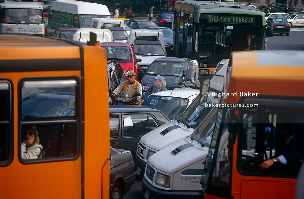 "Near the chaotic road junction of Piazza Venezia in the Italian capital of Rome, we see a gridlock situation of traffic. Buses, cars and three scooters and riders appear to be stuck in the middle of a motoring nightmare as no-one goes anywhere - the progress of this journey to destinations and life itself, has ground to a halt. A bus passenger looks out resigned through her window, a driver on another vehicle rests his hand on a ledge and the riders are sandwiched between cars. The dot matrix sign on the 60 bus it mentions its own destination, the abbreviation for Piazza spelled as ""P.za"". The Piazza Venezia takes its name from the adjacent Palazzo Venezia, the former embassy in the city of the Republic of Venice. The piazza is at the foot of the Capitoline Hill and near the Roman Forum."