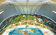 Under the dome: The world's largest indoor beach ... right in the middle of the German countryside<br /> <br /> It is the world's largest indoor beach with 400 sunloungers - and not a cloud in sight.<br /> Yet with up to 6,000 visitors allowed in at a time, there are bound to be towel-fights over them – especially as this 'indoors paradise' is in Germany.<br /> The Tropical Island Resort in Krausnick, south of Berlin also boasts the largest indoor pool, 50,000-plant forest - and enough space to fly a hot air balloon inside.<br /> The former aircraft hangar has been transformed into a paradise offering tourists a tropical escape, if you can ignore the fact that you are miles from any ocean - or the tropics, for that matter.<br /> The gigantic hangar was built to produce transport zeppelins but after the company went bankrupt in 1992 the hangar fell into disuse.<br /> A Malaysian company saw the potential in the hangar, which is the world's largest freestanding building, and Tropical Island Resort opened in 2004.<br /> <br /> Despite the impressive interior of the hot hangar, visitors reviewing the indoor tropical resort on reddit complained about high prices on everything from beverages to accommodation and additional fees to use the popular water slides.<br /> Some users went as far as to vent their disappointment in the type of crowd attracted by the tropical escape.<br /> User Antares42 wrote: 'A good proportion of the audience is folks who'd love to fly to the beach but can't afford it... and it shows,' complaining about 'Mallorca youths - loud, obnoxious, inebriated, strutting about as if they owned the place.'<br /> 'It's nice for families with small kids, but we weren't overwhelmed (3 people in our late 20s)' another Reddit user said.<br /> 'There simply wasn't much fun stuff to do all day, just the pools, even the mediocre slides cost extra.'<br /> The resort, located on an old World War II runway, keeps a pleasant temperature of 26C, thanks to the modified 7