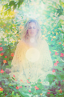 Woman meditating in nature immersed in a line of light circles from seat to crown.