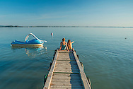 Revfulop, Balaton, Hungary, August 2015.  Tourists swiming in the warm water. Balatontourist Camping Napfény in Révfülöp is situated directly by lake and at few kilometres from the scenic Kali Basin, considered as the most beautiful landscape of  the Northern shore. Lake Balaton is a freshwater lake in the Transdanubian region of Hungary. It is the largest lake in Central Europe and one of the region's foremost tourist destinations. The mountainous region of the northern shore is known both for its historic character and as a major wine region, while the flat southern shore is known for its resort towns. Photo by Frits Meyst / MeystPhoto.com