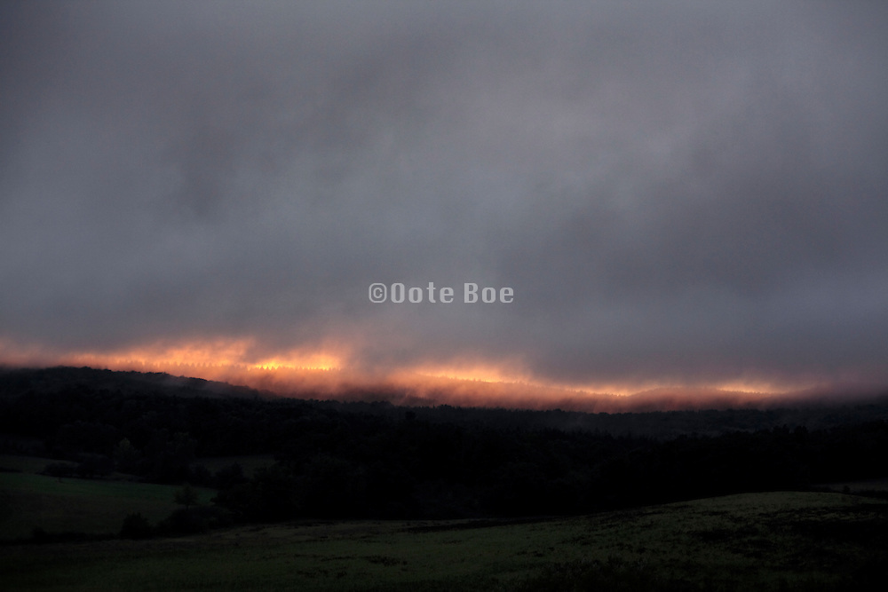 dark setting clouds over rural landscape with tin sliver of light