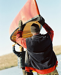 Back of Two men carrying a canoe during the winter
