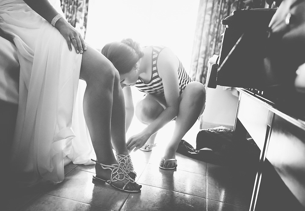 Wedding Photos by Connie Roberts Photography<br />  Bridesmaid helps the bride put on her wedding shoes