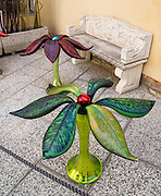 Glass leaves decorate a plant-shaped art work by a stone bench on Murano, Italy. To reduce the threat of fire to Venice, all glassmakers were forced to the island of Murano in 1291 AD. Murano is a series of islands linked by bridges in the Venetian Lagoon, in northern Italy, Europe. Venetian glass is world-renowned as colorful, elaborate, and skillfully made. Once an independent comune, Murano is now a frazione of the comune of Venice. Venice and the Venetian Lagoon are honored on UNESCO's World Heritage List.