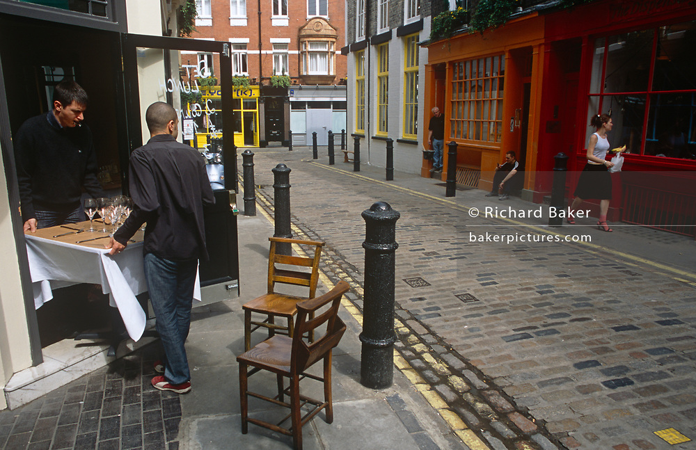 As two workers carefully reverse from a restaurant with a table, one takes his eye off the job in hand and looks admiringly at a passing lady, on 20th May 2002, in Soho, London, England.