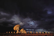 View of some of the dish antennae which make up the Very Large Array (VLA) radio telescope near Socorro, New Mexico. The VLA is the world's largest radio telescope array, consisting of 27 dish antennae, each one 25 meters in diameter. The dishes can be moved to various positions along the arms of a Y-shaped railway network; two of these railway arms are 21 km in length, the third 19 km. The data obtained by the dishes are combined by computer to form a single radio image, so that the 27 antennae in effect form one single giant radio dish. (1984)