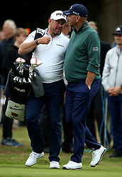 Lee Westwood chats to Thomas Bjorn as he carrying his own clubs after his caddie goes for hot drinks during day two of the British Masters at Walton Heath Golf Club, Surrey.