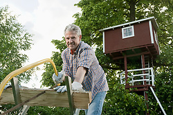 Mature man sawing firewood garden tree-house