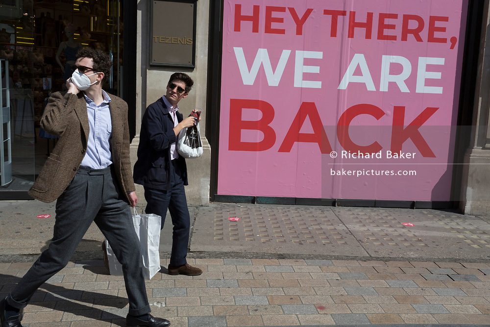 As the UK's Coronavirus lockdown continues to ease, retailers re-open their doors to shoppers, two men walk past the Tenezis shop at Oxford Circus whose window displays the message that they're back, on 18th June 2020, in London, England.