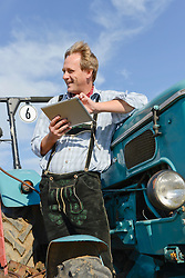 Mature man with digital tablet on tractor, Bavaria, Germany