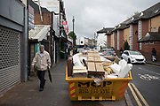 Street scene with a skip full of rubbish and waste on the pavement along the Ladypool Road in Sparkbrook, Birmingham, England, United Kingdom. This area is predominantly inhabited by Asian families. Sparkbrook has the second highest non-white population in Birmingham, with minority ethnic residents living in the area; notably it is home to a large Somali population. Sparkbrook is also the location of Birminghams Balti Triangle, as many of the residents have their own balti businesses.