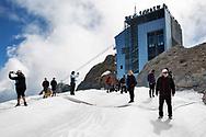 Turisti sul ghiacciaio della Marmolada. Il ghiacciaio è ricoperto da teli protettivi bianchi. Grazie agli impianti è molto facile raggiungere la cima e sono molti i turisti che si spingo fino quassù. Trentino, Agosto 2020.