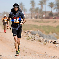 27 March 2007: #425 Tobias Joos of Germany runs across the gorge of El Maharch during third stage of the 22nd Marathon des Sables between jebel El Oftal and jebel Zireg (20.07 miles). The Marathon des Sables is a 6 days and 151 miles endurance race with food self sufficiency across the Sahara Desert in Morocco. Each participant must carry his, or her, own backpack containing food, sleeping gear and other material.