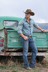 cowboy standing by an old truck on a ranch