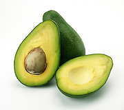 a cut and a whole avocado on white background