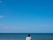 A woman wearing a flowery dress looks out to sea from the promenade on 7 May 2020 in Saltburn-by-the-Sea, Cleveland, United Kingdom. Since the UK government imposed a countrywide lockdown on the evening of 23rd March one of the permitted reasons for leaving home is for daily exercise
