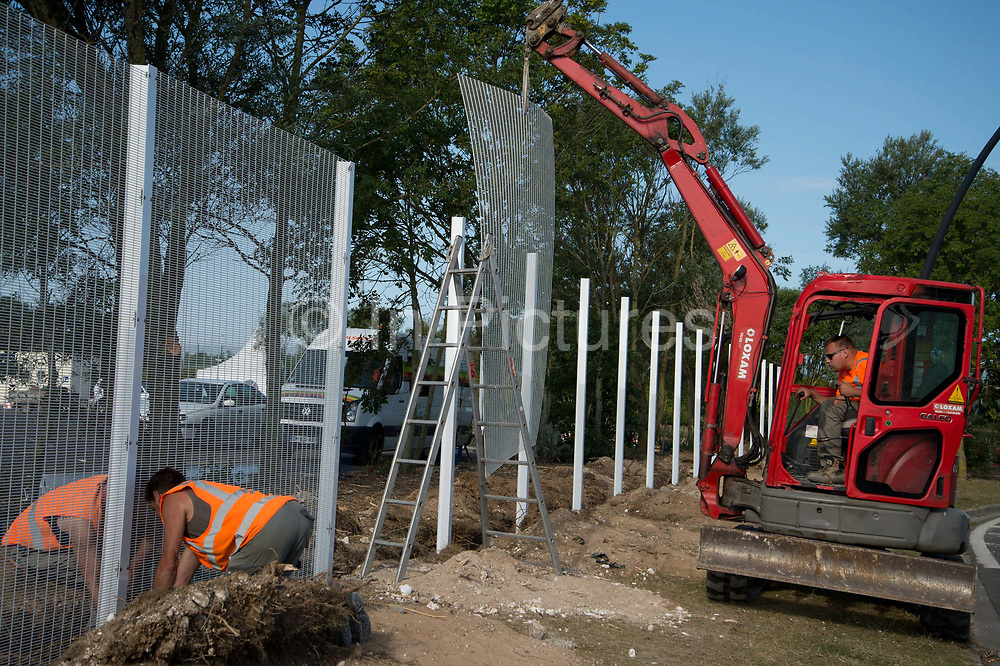 Calais August 2015 . Workmen erect a new fence near the entrance to the Eurotunnel to prevent refugees trying to board trucks to cross the Channel