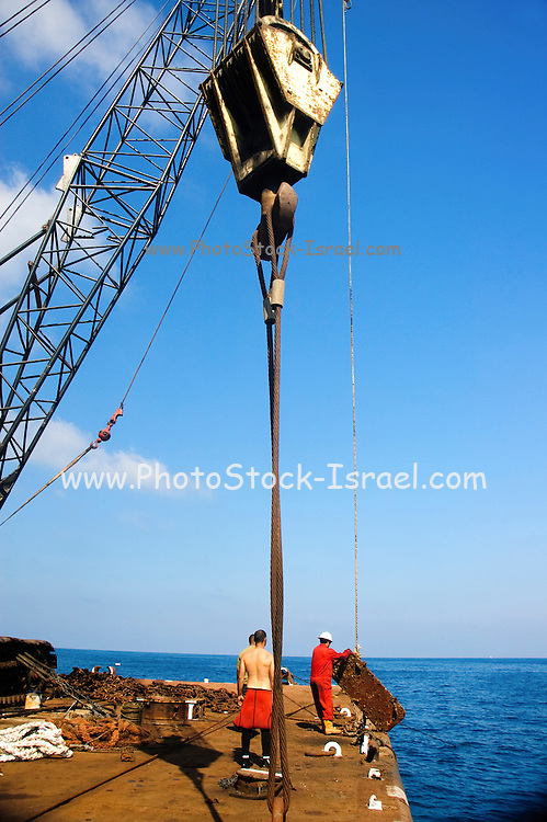 """Israel, Bay of Haifa, Offshore rig salvages the remains of the Israeli cargo vessel """"Shelly"""" that sunk 3km from the harbour after a collision with a passenger ship on August 31 2007. Crane operator on the barge lifting a door out of the sea"""