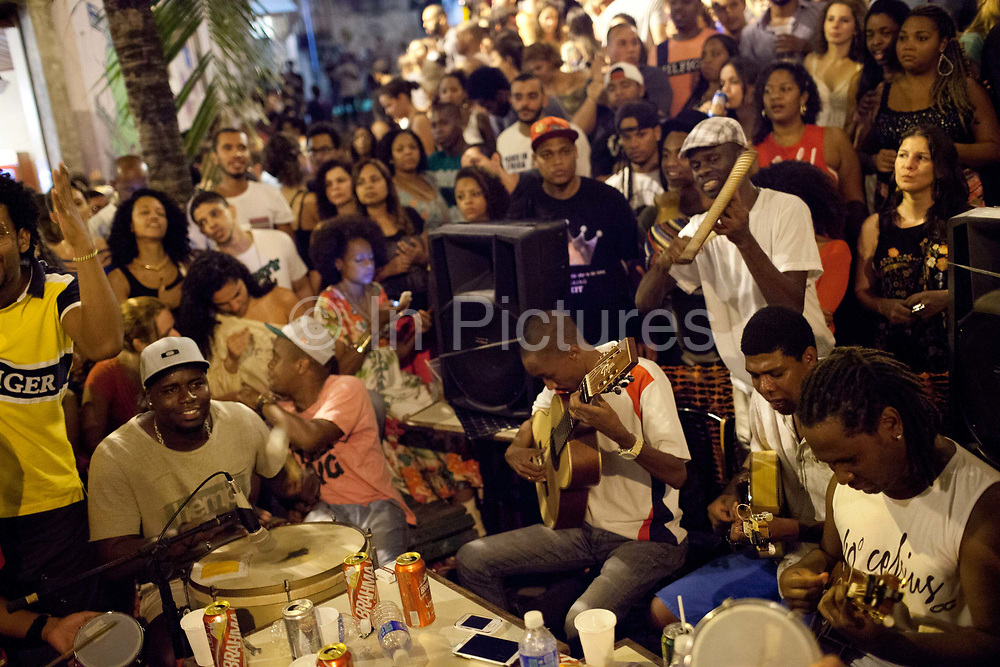 Samba musicians playing with crowd around them, Pedra do Sal, the birthplace of Samba, in Gamboa district which was the neighbourhood where the ex slaves lived after abolition, sometimes referred to as the first favela. Rio de Janeiro, Brazil