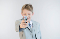 Boy holding toy gun and playing gangster, smiling, portrait