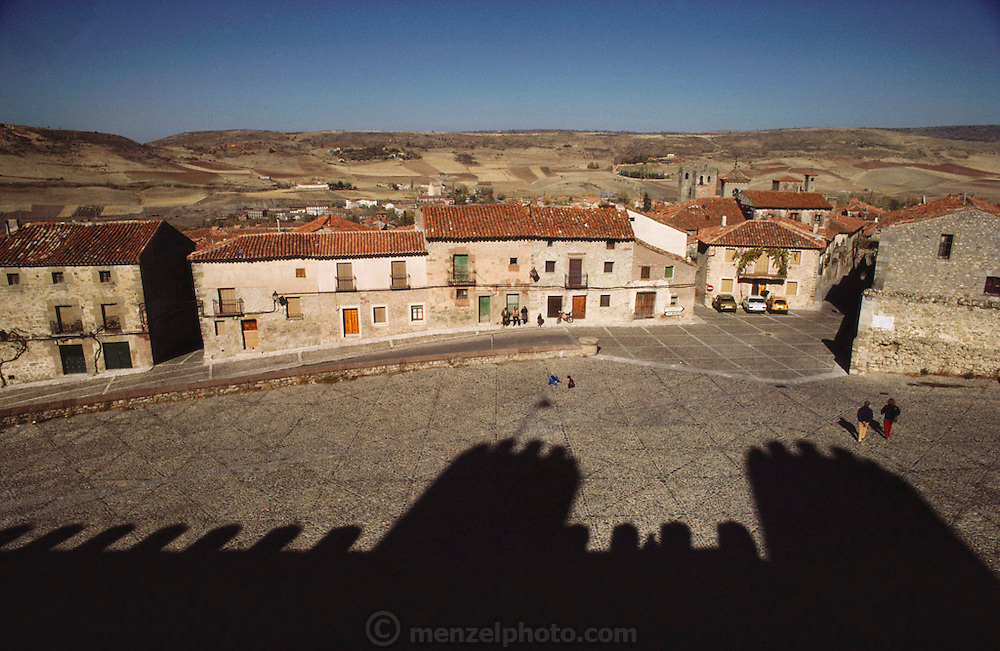 Siguenza, Spain with the shadow of the castle walls in the foreground.