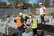 A group of builders laying foundations on new house construction site in Norwich. Norfolk. United Kingdom