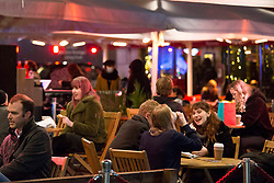 © Licensed to London News Pictures.14/12/2020. London, UK. Despite the rainy weather Londoners are seen enjoying themselves in Covent Garden, before London will go into Tier 3 on Wednesday. Photo credit: Marcin Nowak/LNP