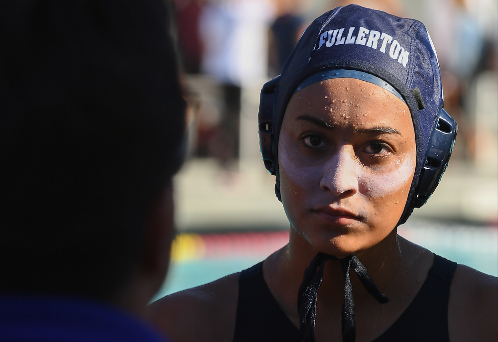 Fullerton College Freshman #6 Bianca Vera gets direction from head coach Gabriel Martinez during half-time. Fullerton won the first round match 17-3 over Cypress College during the Orange Empire Conference water polo championships. November 3rd, 2016.