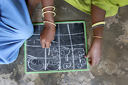 The preschool in ICHHAPUR village. A child writing letters and numbers on a slate board. They are sitting on the balcony area of their small class room. This is one of many supported kindergartens that PREM works with in villages in Orissa and Andhra Pradesh states of India.