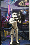 """March, 19th, 2020 - Paris, Ile-de-France, France: Disney shop and Storm Trooper, on empty Avenue des Champs Elysees in Paris, on the third day of a near total lockdown imposed in France. All journeys outside the home unless justified for essential professional or health reasons are outlawed. Anyone flouting the new regulations is punished with monetary fines. French police control of citizens and inspection of valid papers allowing citizens to travel. The most extreme measures so far in France to control the spread of the Coronavirus. Earlier in the week, President of France, Emmanuel Macron, said that citizens must stay at home from midday on Tuesday for at least 15 days. He said """"We are at war, a public health war, certainly but we are at war, against an invisible and elusive enemy"""". Nigel Dickinson"""