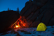 Obadiah Reid (l-r), Marco Binotti, and David Coffey keep warm by a campfire in their cave camp in McMurdy Park, Lost Creek Wilderness, Colorado.
